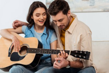 Man embracing smiling girlfriend while playing acoustic guitar together
