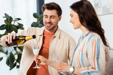 Selective focus of smiling man pouring champagne in glass near beautiful girlfriend at home stock vector