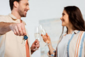 Selective focus of man holding keys of new house and toasting champagne with smiling girl