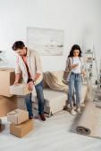 Muž drží lepenkovou krabici, zatímco přítelkyně pomocí smartphone v obývacím pokoji během stěhování