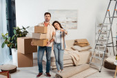 Photo Positive woman holding keys of new house near boyfriend with cardboard boxes in living room