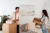 Smiling girl holding pizza box near boyfriend holding cardboard box in new house