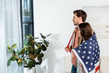 Side view of smiling woman wrapping in american flag standing near boyfriend at home stock vector