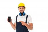 Usmívající se dělník v uniformě a ochranné přilbě ukazující prstem na smartphone izolovaný na bílém