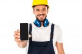 Selektivní zaměření usmívajícího se dělníka zobrazující smartphone s prázdnou obrazovkou izolovanou na bílé
