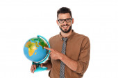 Photo Bearded teacher smiling at camera while pointing with finger at globe isolated on white