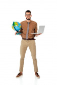 Positive teacher in eyeglasses holding globe and laptop while looking at camera on white background
