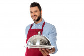 Selective focus of smiling bearded waiter holding tray and cloche isolated on white