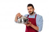 Hübscher Kellner in Schürze mit Metalltablett und Tellerdecke, während er isoliert auf weiß in die Kamera blickt