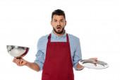 Schockierter Kellner in Schürze hält Tablett und Cloche isoliert auf weißem Grund