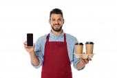 Schöner Kellner lächelt in die Kamera, während er Pappbecher und Smartphone mit leerem Bildschirm auf Weiß hält