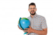 Smiling nerd looking at camera while holding globe isolated on white