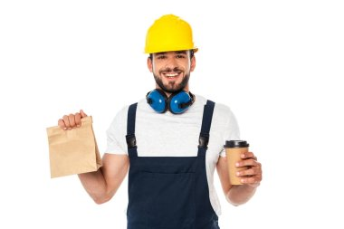 Handsome workman holding coffee to go and paper bag and smiling at camera isolated on white stock vector