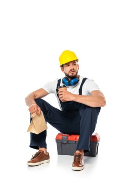 Handsome workman holding coffee to go and paper bag while sitting on toolbox on white background stock vector