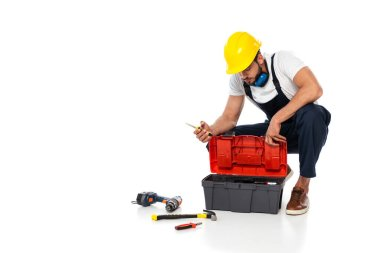 Workman in hardhat and ear defenders holding screwdriver near tools and toolbox on white background stock vector