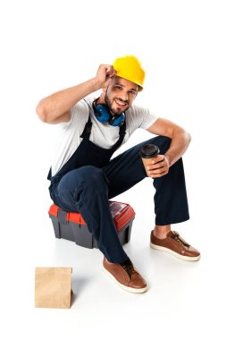 Smiling workman in uniform and hardhat holding coffee to go while sitting on toolbox near paper bag on white background stock vector