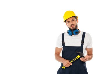 Handsome workman in uniform and hardhat holding hammer and looking at camera isolated on white stock vector