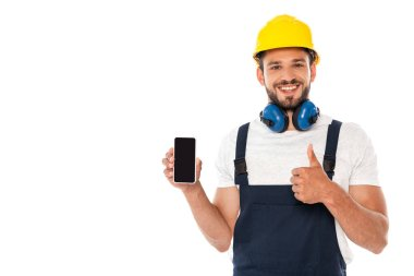 Smiling handyman in workwear showing like gesture while holding smartphone with blank screen isolated on white stock vector