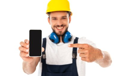 Selective focus of smiling repairman pointing with finger at smartphone with blank screen isolated on white stock vector
