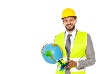 Smiling engineer in formal wear and hardhat holding globe isolated on white stock vector