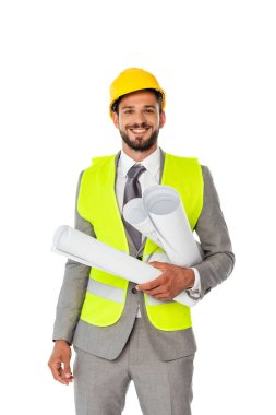 Handsome positive engineer in suit and safety vest holding blueprints and looking at camera isolated on white stock vector