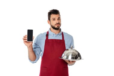 Handsome waiter holding smartphone and tray with cloche isolated on white stock vector