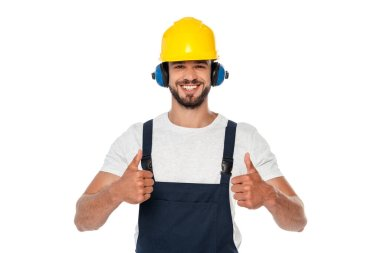 Handsome smiling builder in uniform showing thumbs up at camera isolated on white stock vector