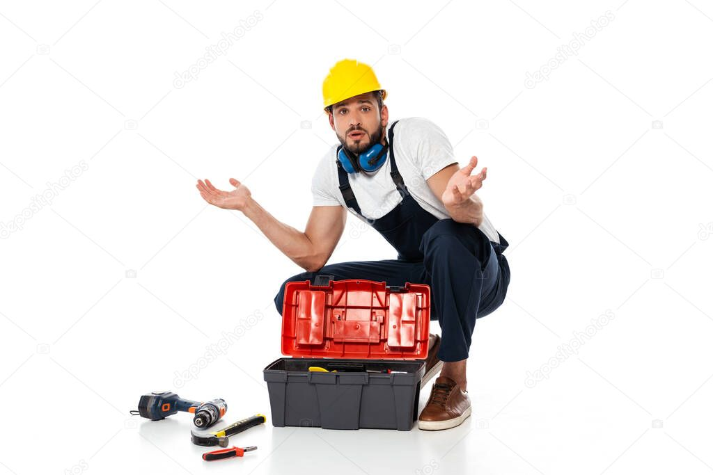 Confused workman showing shrug gesture near tools and toolbox on on white background stock vector