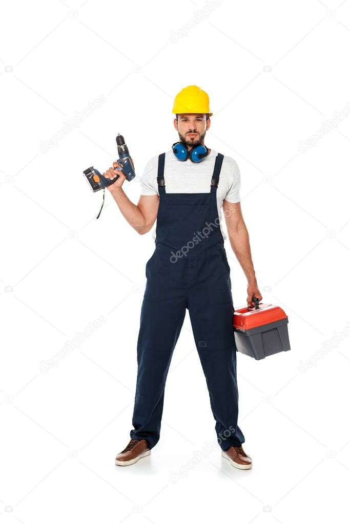 Handsome workman in uniform and hardhat holding electric screwdriver and toolbox on white background stock vector
