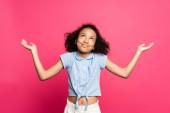 mosolygós aranyos göndör afro-amerikai gyerek bemutató vonós gesztus elszigetelt rózsaszín