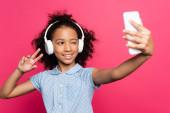 szelektív fókusz mosolygós göndör afro-amerikai gyerek fejhallgató mutatja győzelem jele, miközben selfie okostelefon elszigetelt rózsaszín