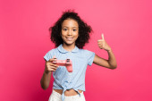 KYIV, UKRAINE - Június 9, 2020: mosolygós aranyos göndör afro-amerikai gyerek joystick mutatja hüvelykujját fel elszigetelt rózsaszín