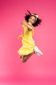 side view boldog göndör afro-amerikai gyermek sárga ruhában ugrás és mutatja hüvelykujját fel rózsaszín háttér
