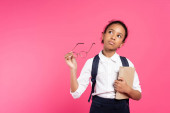 Photo pensive african american schoolgirl with book and glasses isolated on pink