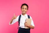 mosolygós afro-amerikai iskolás lány könyvvel mutatja hüvelykujját fel elszigetelt rózsaszín