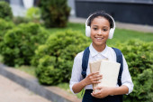 smiling african american schoolgirl in headphones with backpack and books outdoors