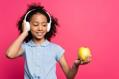 smiling curly african american kid in headphones holding apple isolated on pink