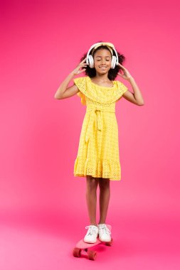 Full length view of smiling curly african american child in yellow outfit and headphones on penny board with closed eyes on pink background stock vector