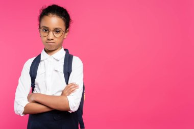 offended african american schoolgirl in glasses with backpack and crossed arms isolated on pink