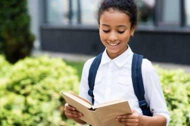 Smiling african american schoolgirl reading book outdoors stock vector