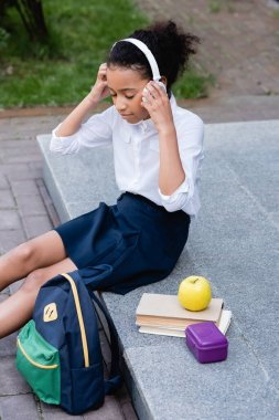 african american schoolgirl listening music in headphones near backpack, books and lunch outdoors