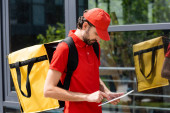 Courier with thermo backpack using digital tablet on urban street