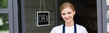 Panoramic shot of smiling waitress looking at camera near signboard with open lettering on door of cafe stock vector