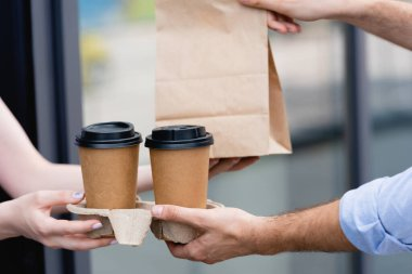 Cropped view of waitress giving coffee to go and paper bag to customer near cafe on urban street