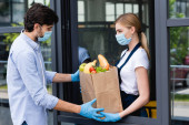 Boční pohled muže s nákupní taškou s ovocem a zeleninou od prodavačky u okna