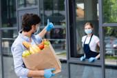 Válogatott fókusz férfi gazdaság bevásárló táska és mutatja hüvelykujját fel, miközben nézett eladó a városi utcán