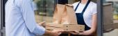 Panoráma felvétel egy férfiról, aki pizzás dobozokat és papírzacskókat kap elvitelre a pincérnőtől a kávézó ablaka közelében.