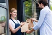 Vonzó eladó nő, aki papírzacskókat ad a férfinak a kávézó ajtaja közelében.