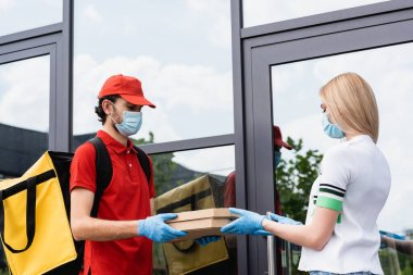 Courier in medical mask and latex gloves giving pizza boxes to woman near building on urban street stock vector