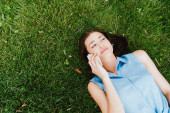 von oben: Mädchen liegt auf grünem Gras und spricht auf Smartphone